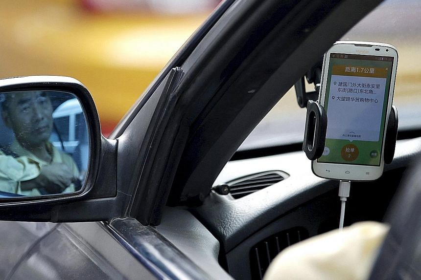 A driver using the Didi Chuxing car-hailing application in Beijing on Sept 22. Industry players are betting that the ride-hailing market in China will become the biggest in the world.