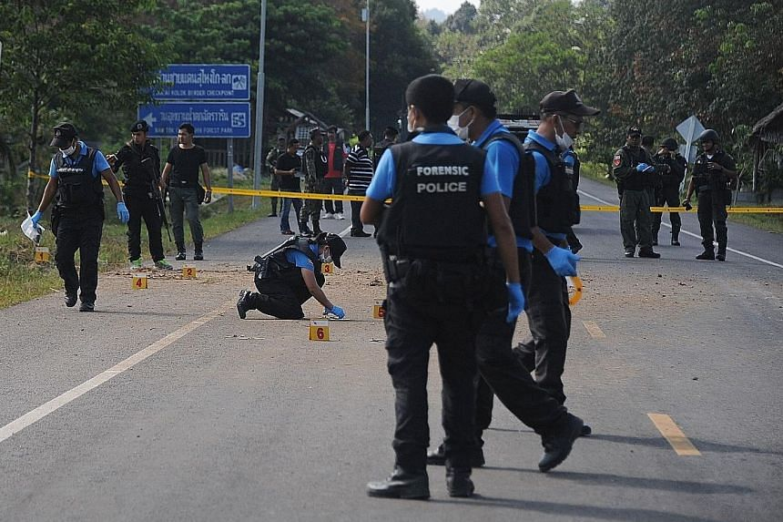 Thai bomb squad members inspecting the site of a roadside bomb attack on Sunday in the Cho-airong district of Narathiwat.
