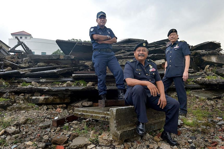 "(From left) Senior Warrant Officers Isnin Ghani, Mohd Salleh Ali and Jimmy Tan at the Civil Defence Academy's field training area, where ""ruins"" made of concrete slabs and debris simulate a collapsed structure. They dug a tunnel with their hands and"