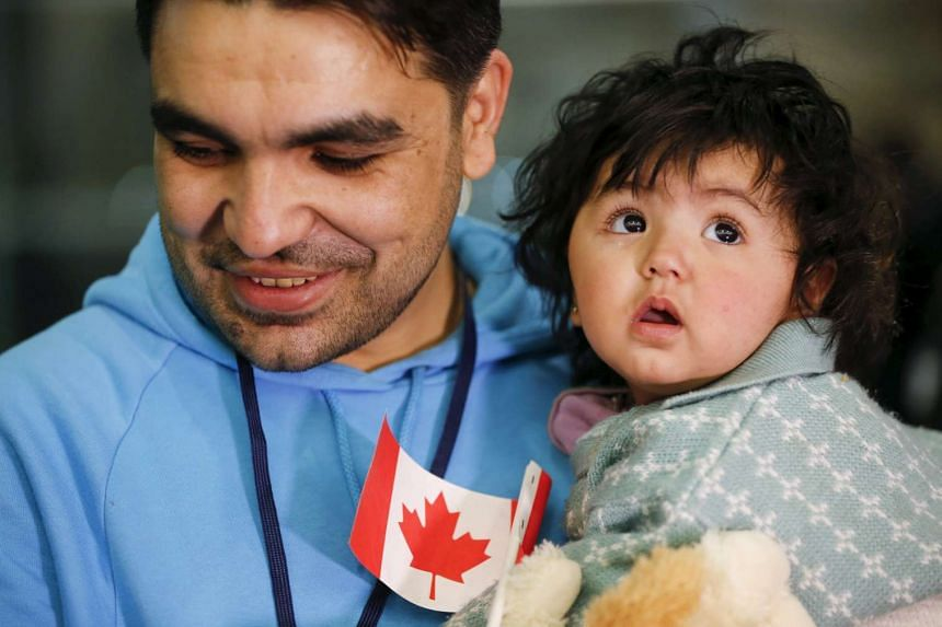 A Syrian refugee holds his daughter as they arrive at the Pearson Toronto International Airport in Mississauga in December last year.