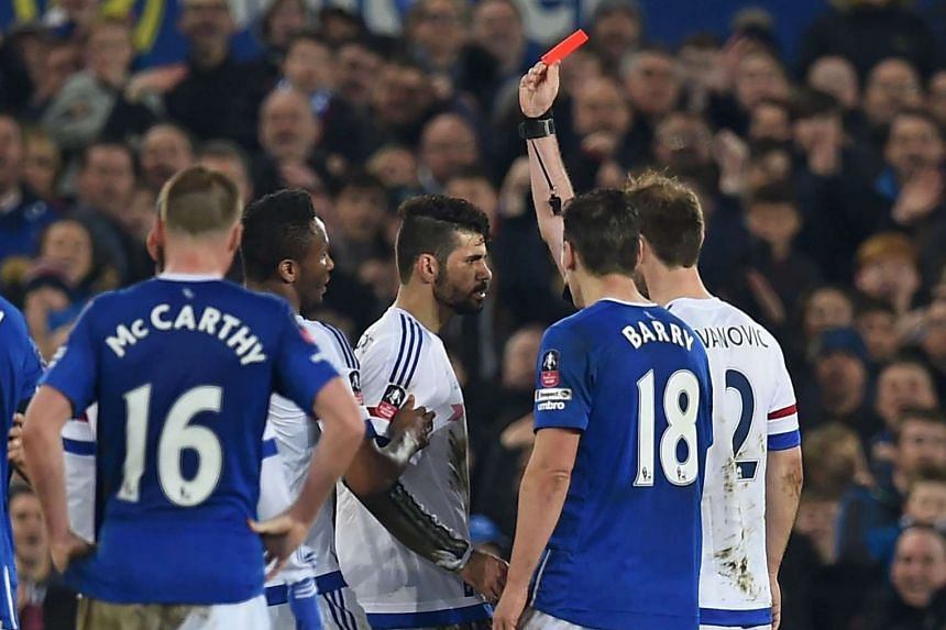 Chelsea striker Diego Costa (centre) is shown a red card by referee Michael Oliver during the English FA cup match against Everton at Goodison Park on March 12, 2016.