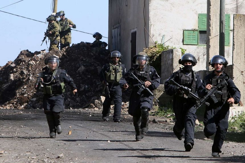 Israeli security forces running during clashes with Palestinian protesters in the village of Kfar Qaddum, near Nablus, in the occupied West Bank, on March 11, 2016.