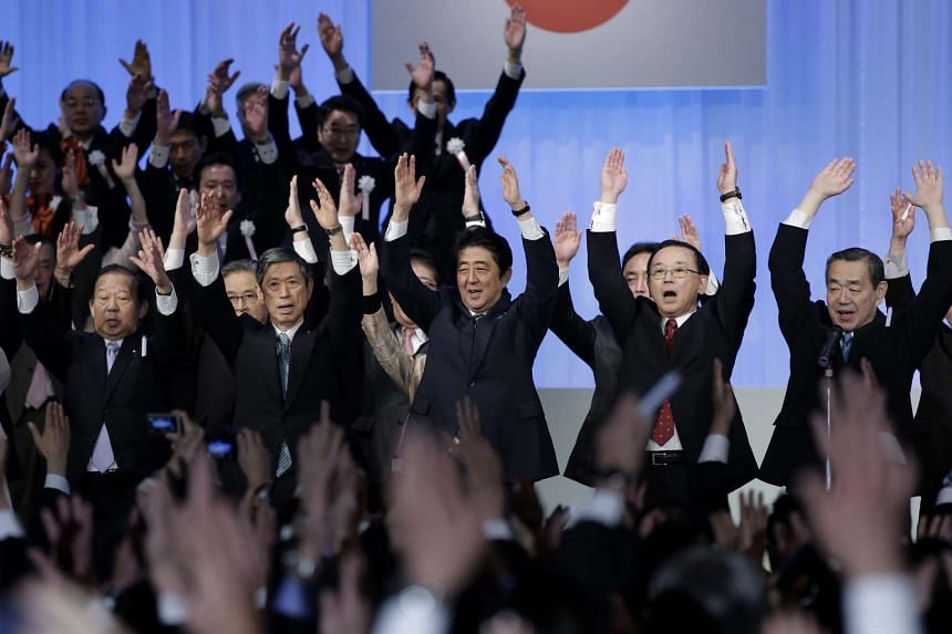 Japanese Prime Minister Shinzo Abe (centre) cheering with members of the ruling LDP at the party's 83rd annual convention in Tokyo on March 13, 2016.