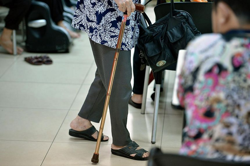 An elderly woman walking with the aid of a walking stick.