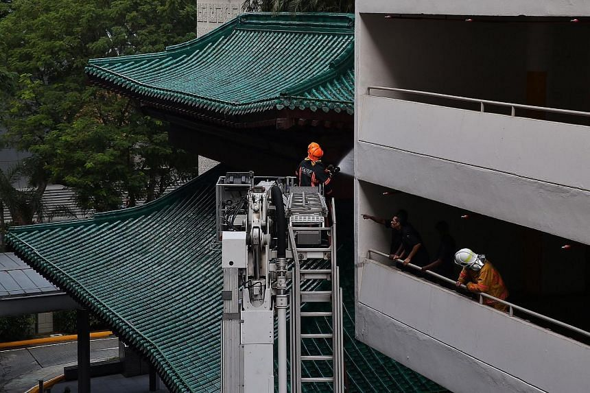 SCDF hosing down the affected rooftop area after a fire broke out at Tang Plaza on March 15, 2016.