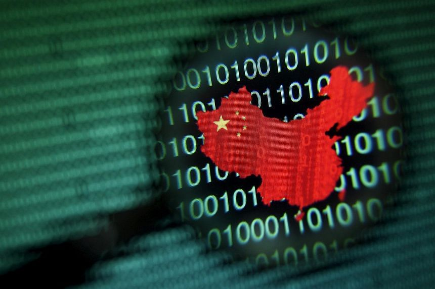 A map of China is seen through a magnifying glass on a computer screen showing binary digits.