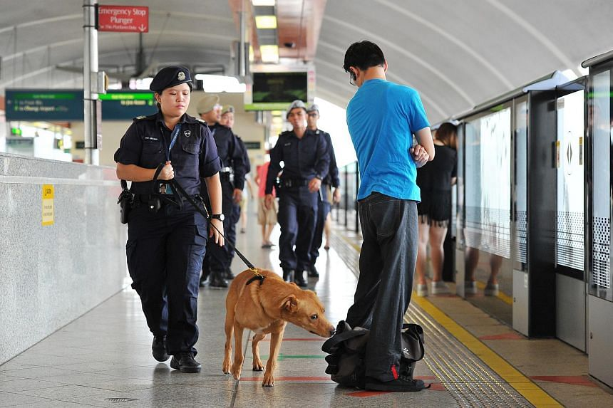 A police officer patrolling Bedok MRT station with a dog on Aug 8, 2015.