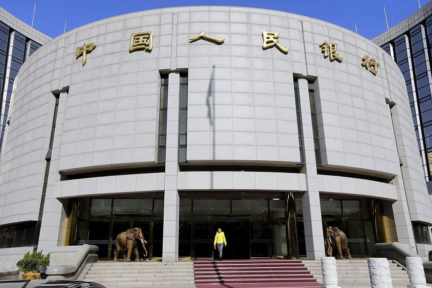 A woman walks out of the headquarters of the People's Bank of China in Beijing, China.