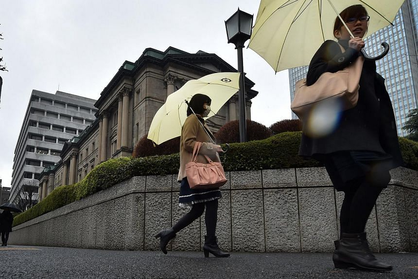 Pedestrians walking past the Bank of Japan headquarters in Tokyo on March 14.