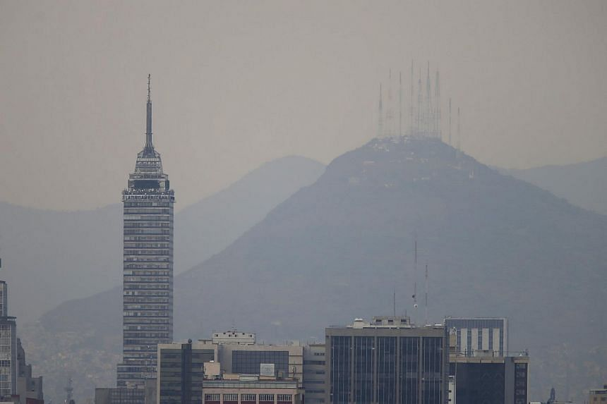 Buildings stand shrouded in smog in Mexico City, on March 14, 2016.