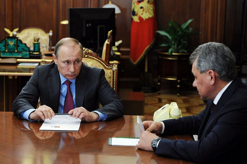 Mr Putin meeting with Russian Defence Minister Sergei Shoigu (right) and Foreign Minister Sergei Lavrov (not in picture) at the Kremlin on March 14.