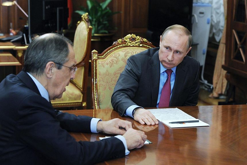 President of Russia Vladimir Putin (right) listens to Russian Minister of Foreign Affairs Sergey Lavrov in the Kremlin, Moscow, on March 14, 2014.