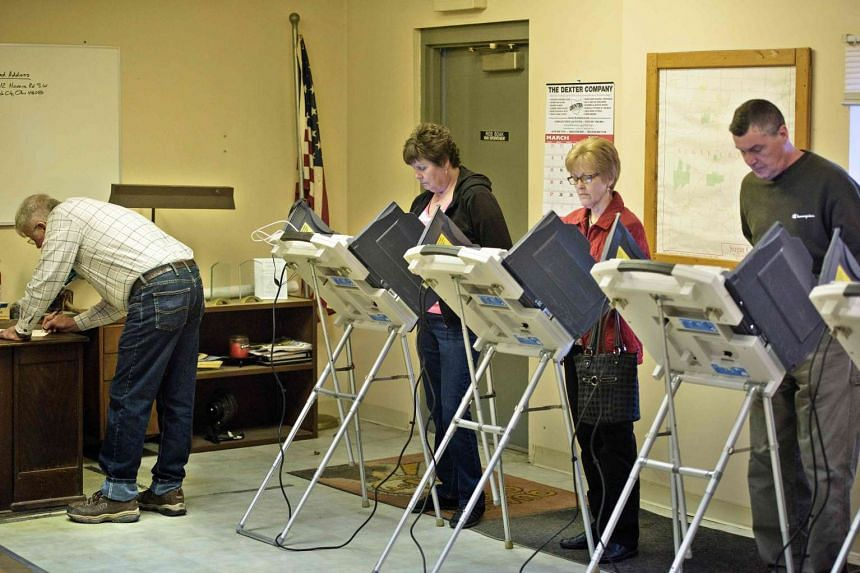 Voters use electronic machines to vote at a polling place in Stark County on March 15, 2016.