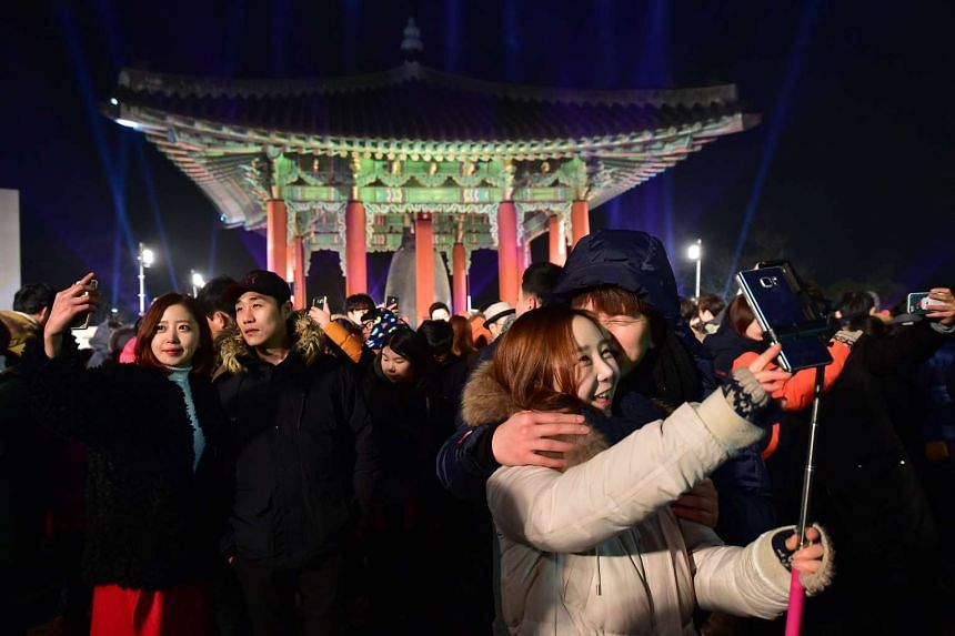 South Korean couples taking selfies during a New Year's Day countdown at Imjingak Peace Park in Paju on Dec 31, 2015.