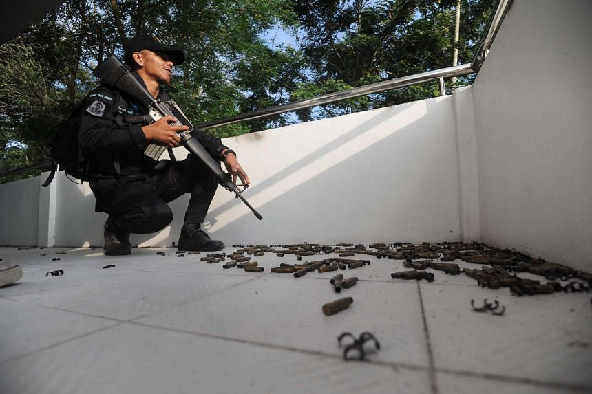 A ranger holds his weapon as he kneels by cartridges left at a hospital building from where suspected separatist militants launched an ambush in Narathiwat, Thailand, on March 14, 2016.