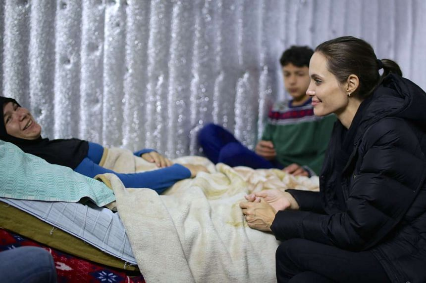 A handout picture made available by the United Nations High Commission for Refugees on March 15, 2016 shows UNHCR special envoy US actress Angelina Jolie meeting with Syrian refugees during her visit to a Syrian refugee camp near the city of Zahle in