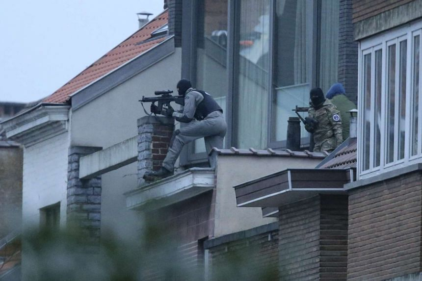 Security forces taking position during a police operation in the Forest municipality of Brussels, Belgium, on March 15, 2016.
