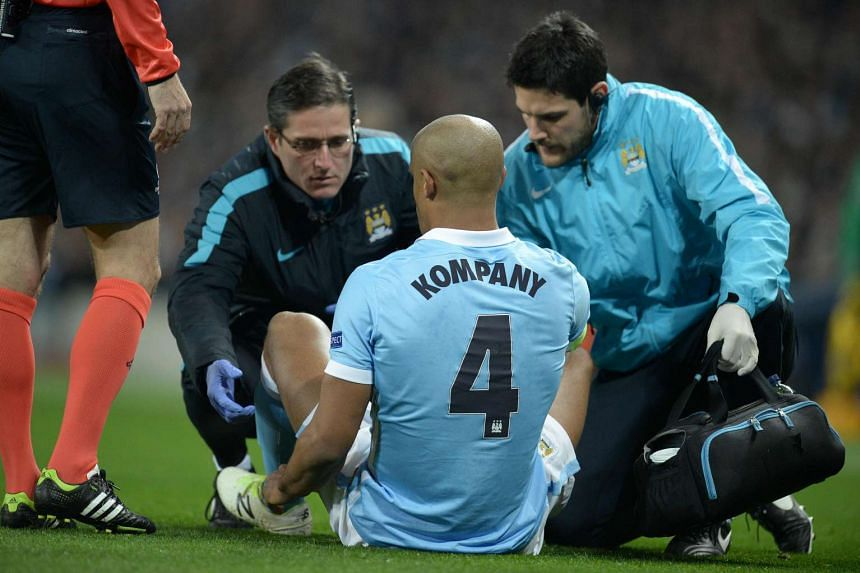 Manchester City's Vincent Kompany receives medical treatment before leaving the pitch injured.