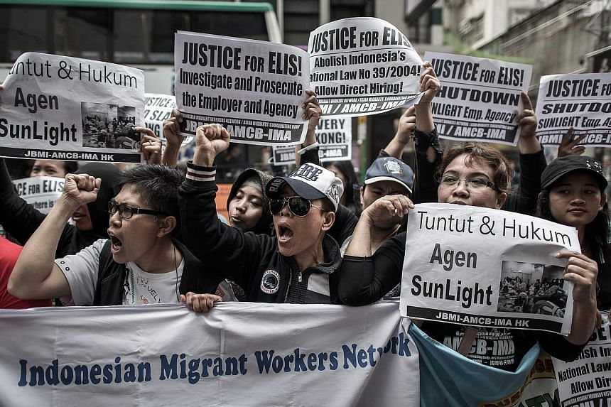 Protesters shouting slogans for migrant workers' rights outside an employment agency in Hong Kong last year. One in three households with children in Hong Kong employs a foreign domestic worker, who works an average of over 70 hours a week.