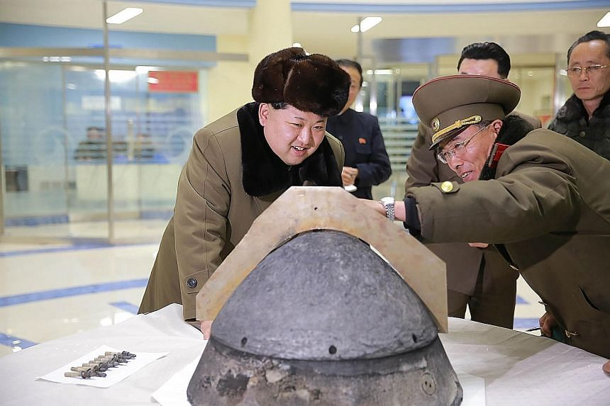 North Korean leader Kim being shown part of a locally-made missile warhead in an undated picture released by the country's official news agency yesterday. The North has issued belligerent statements almost daily since new UN sanctions kicked in this