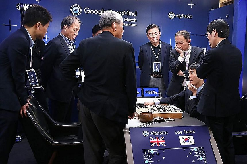 South Korean Go master Lee Se Dol (seated), one of the greatest modern players of the ancient board game, reviewing the game after he lost the fifth and final round against the supercomputer AlphaGo created by Google company DeepMind, in Seoul yester