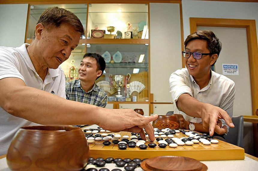 (From far left) SWA head coach Yang Jin Hua, 64, and Weiqi enthusiasts Ho Jia Xuan, 29, and Kenneth Ng, 30, enjoying a game of Weiqi, or Go, as they watched a live streaming of the game between Mr Lee Se Dol and supercomputer AlphaGo.