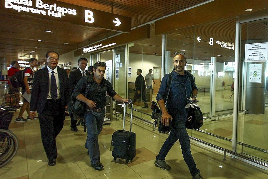 ABC cameraman Eroglu (left) and reporter Besser (with trolley bag) at Kuching International Airport, Sarawak, yesterday. Earlier, they had been told they would face a criminal charge that could land them in jail for two years.