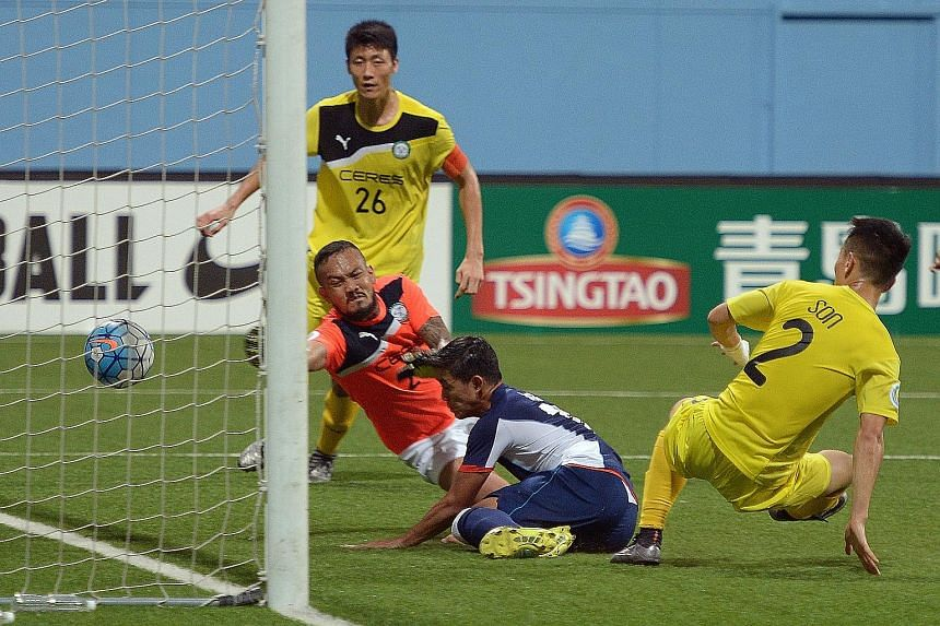 Tampines' Hafiz Abu Sujad bundling the ball home despite the vain attempts of defender Kim Sang Min (No. 26), goalkeeper Louie Michael Casas and defender Son Yong Chan (No.2) to keep it out.