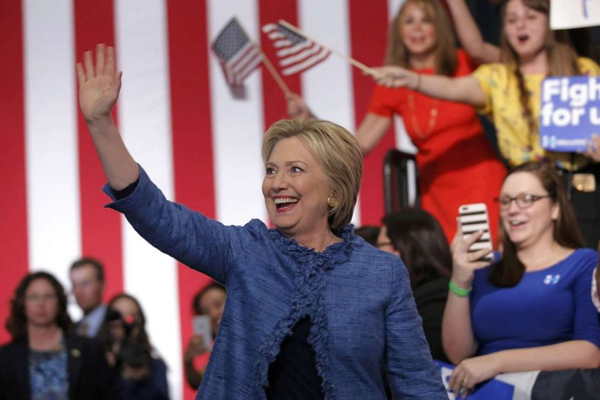 Democratic US presidential candidate Hillary Clinton waves as she arrives to speak to supporters at a campaign rally in West Palm Beach, Florida on March 15, 2016.