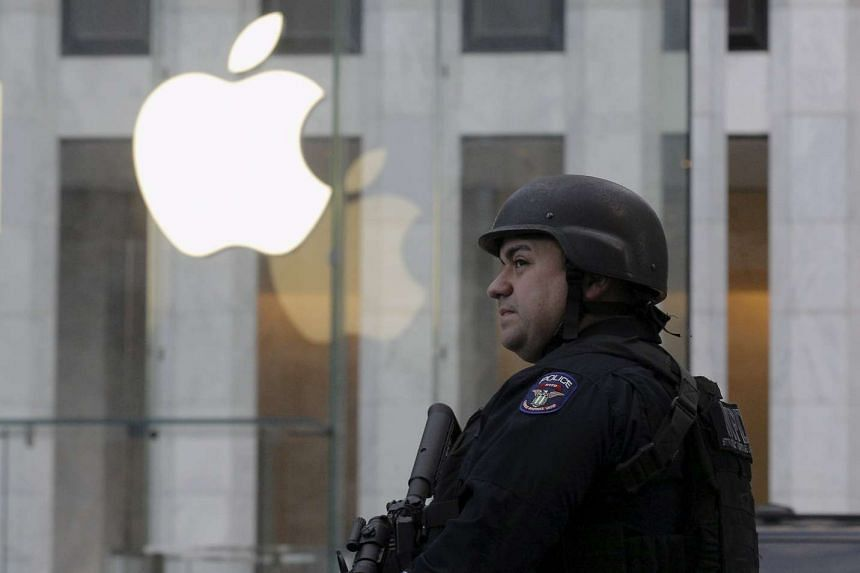 A New York City police officer stands across the street from Apple Store on 5th Ave in New York, March 11, 2016.