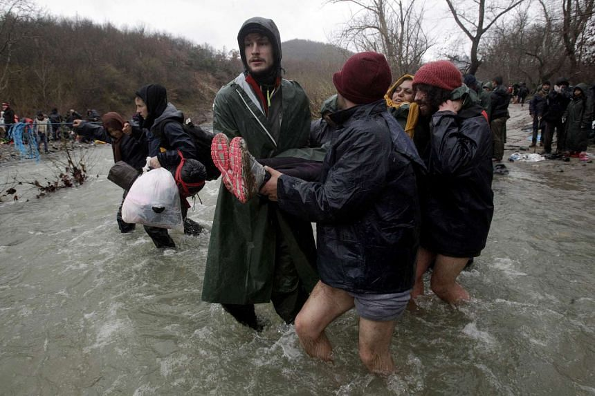 Refugees and migrants cross a river to return to Greece after an unsuccessful attempt to enter Macedonia.
