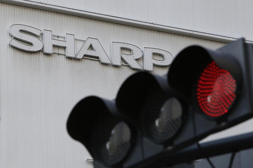 A logo of Sharp is seen behind a traffic signal of red outside an electronics retail store in Tokyo, Japan, on Feb 26, 2016.
