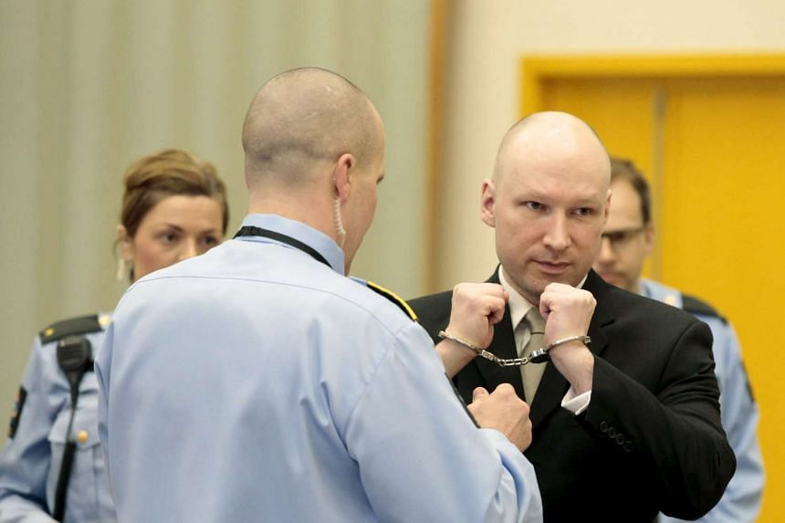 Mass murderer Anders Behring Breivik getting his handcuffs removed inside the court room in Skien prison, Norway, on March 16, 2016.