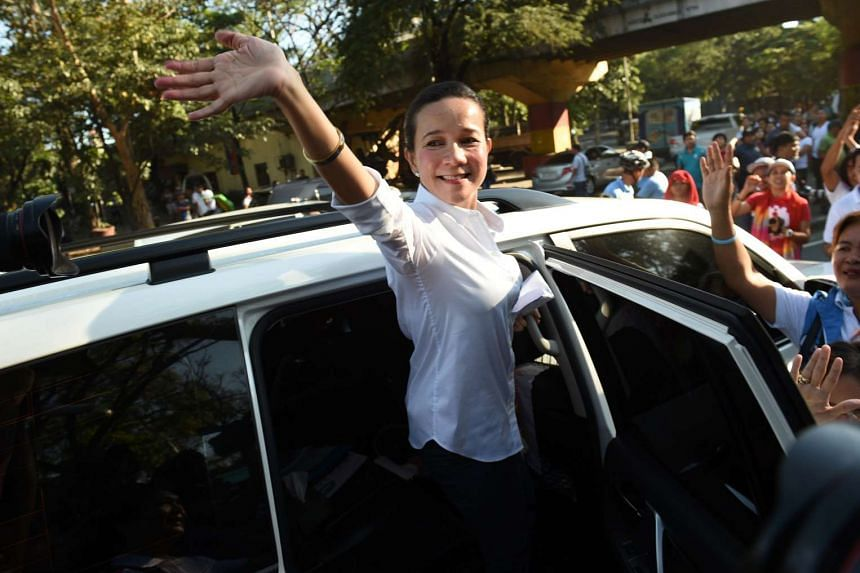 Philippine presidential candidate Grace Poe waving to supporters and members of Gabriela women's group, during a rally to celebrate International Women's Day in Manila, on March 8, 2016.