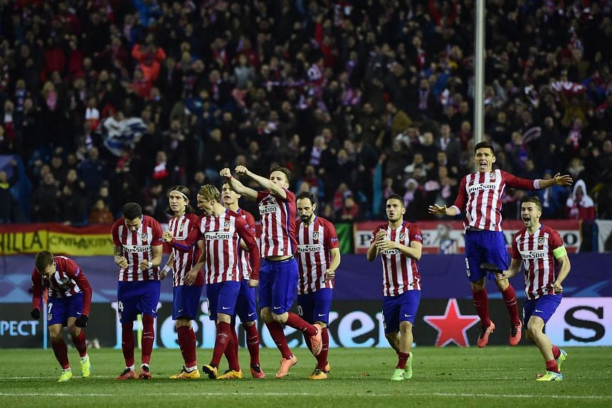 Atletico Madrid players celebrate after winning the penalty shoot-out against PSV Eindhoven.