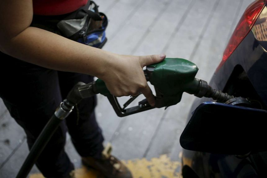 A worker pumps petrol into a vehicle in Caracas, Venezuela.