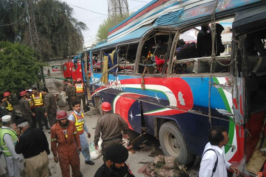Pakistani police officials searching a damaged bus after a bomb blast in Peshawar on March 16, 2016.