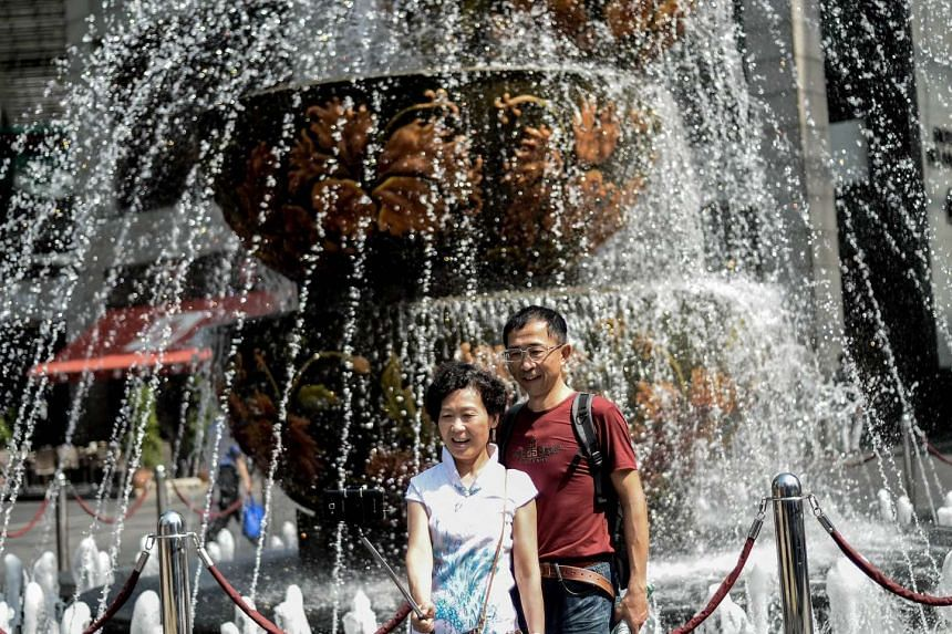 Tourists taking a selfie in front of a fountain outside a popular shopping mall in Kuala Lumpur, on Feb 23, 2016.