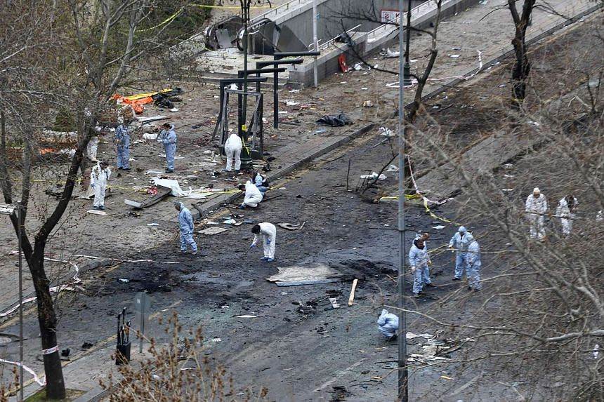 Forensic experts investigating the scene of an explosion on March 14, 2016, the day after a suicide car bomb ripped through a busy square in central Ankara killing at least 34 people and wounding 125, officials said.