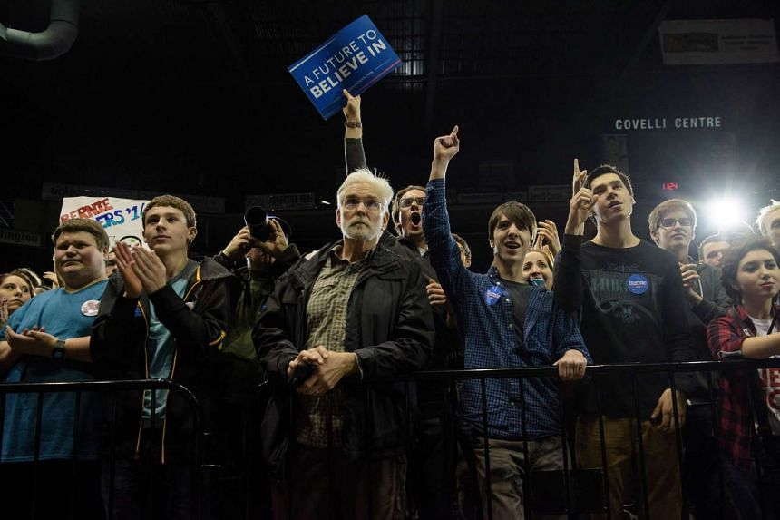 People cheer as US presidential hopeful Senator Bernie Sanders speaks at a rally in Youngstown, Ohio, on March 14, 2016.