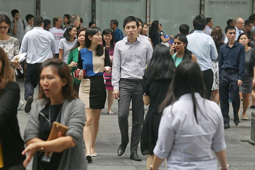 Office workers walking outside Raffles Place MRT station.