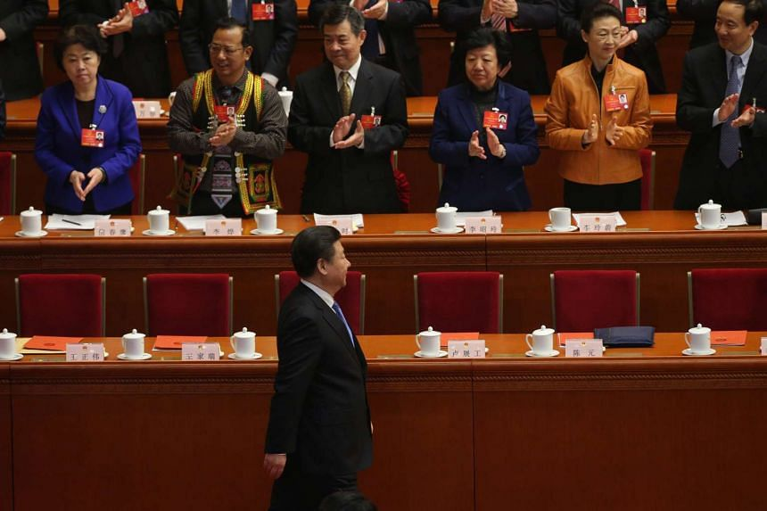 Chinese President Xi Jinping arrives during the closing of the fourth session of the 12th National People's Congress at the Great Hall of the People in Beijing.