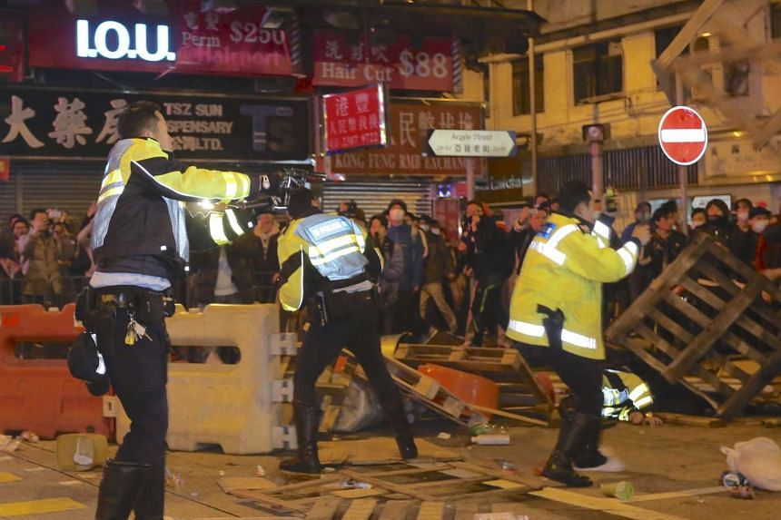 A policeman (left) points his pistol during a clash at Mongkok district in Hong Kong, on Feb 9, 2016.