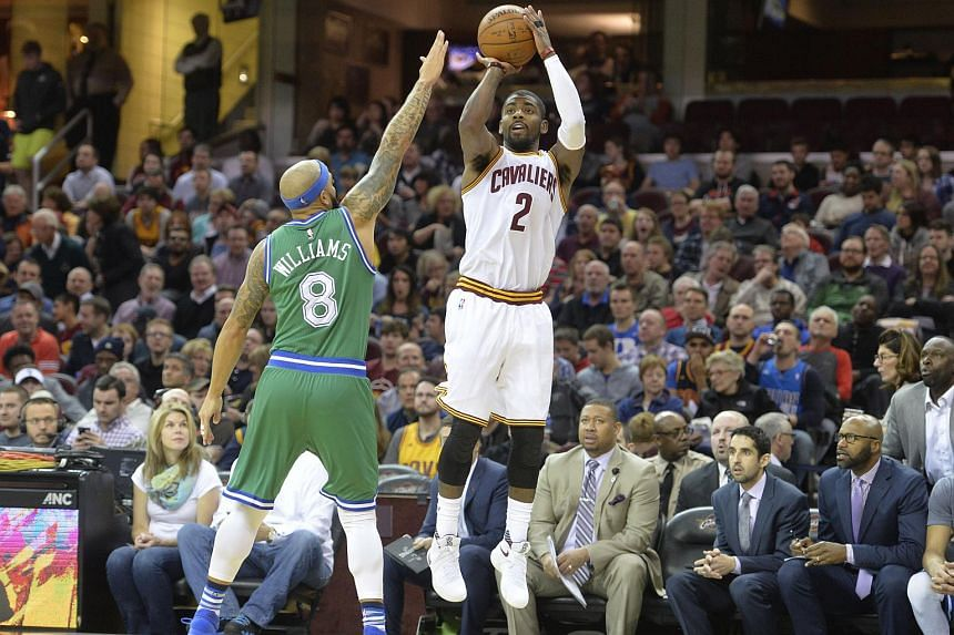 Cleveland Cavaliers guard Kyrie Irving (right) shooting over Dallas Mavericks guard Deron Williams at Quicken Loans Arena on March 16, 2016.