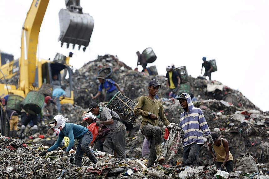 People searching through garbage looking for material to recycle at Bantar Gebang landfill in Bekasi, West Java province, on March 2, 2016.