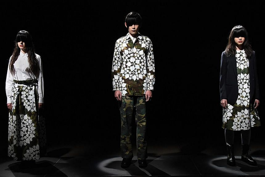 Models in floral silkscreen-printed garments and combat boots by Japanese designer Tsukasa Mikami at Tokyo Fashion Week.