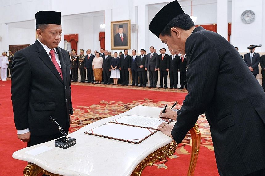 President Joko signing the documents during the swearing-in ceremony of General Tito as the new chief of the national counter-terrorism agency yesterday at the presidential palace in Jakarta.