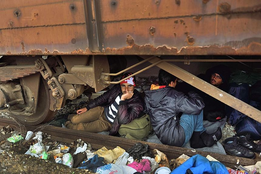 Refugees taking shelter under a train carriage at a camp at the Greek- Macedonian border yesterday, where thousands of refugees and migrants are stranded