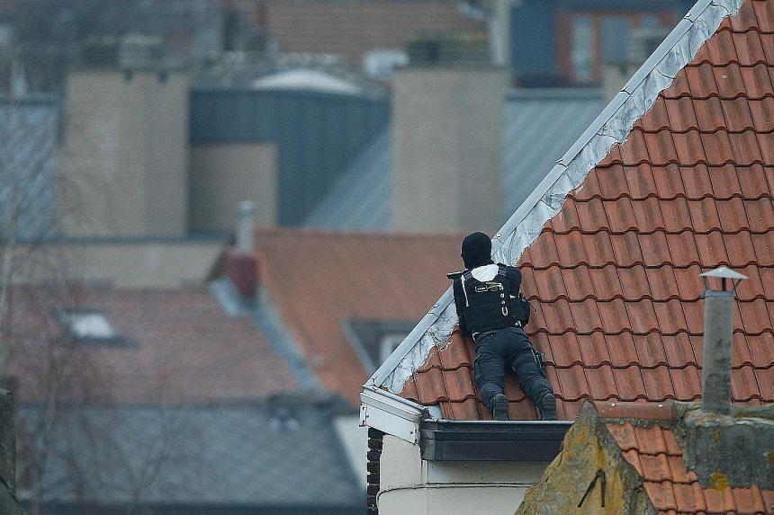 An officer on a rooftop during the police operation in Forest, Brussels, on Tuesday. The anti-terror raid was linked to the Paris attacks last November.