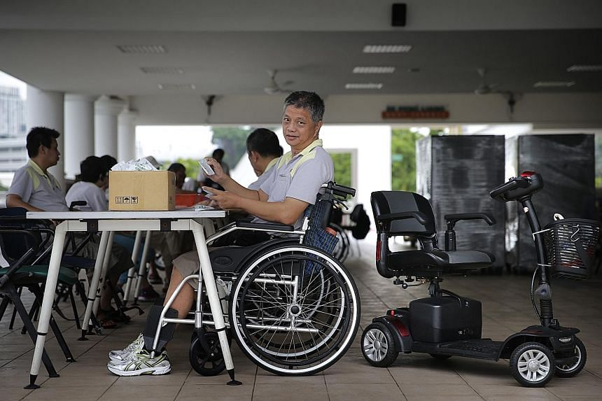 SPD trainee Lim Tow Chong packing goodie bags. He goes to the workshop on a motorised scooter but transfers to a wheelchair for his job. Mr Lim is among a group of workers aged 18 to their 60s who have physical or development disabilities, or visual